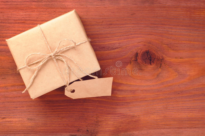 Gift box into brown paper tied by twine with blank tag on old wooden table with space for text. Rustic gift box packed into brown paper tied by twine with blank stock photography