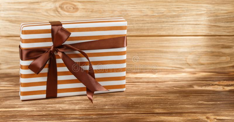 Gift box with ribbon on wooden background top view. stock photo