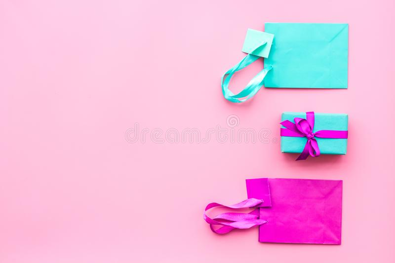 Gift box and colorful paper bag on pink background top view mock-up stock photography