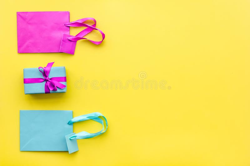 Gift box and colorful paper bag on yellow background top view space for text stock photo
