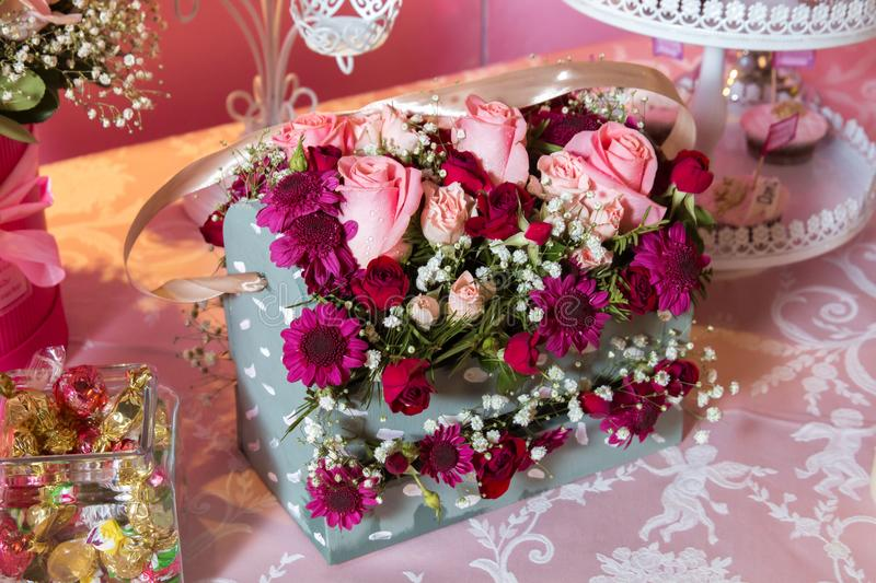 Gift box with colorful roses. Four-cornered birthday flower bouquet. Bouquets of paper flowers in a cardboard square boxes royalty free stock photography