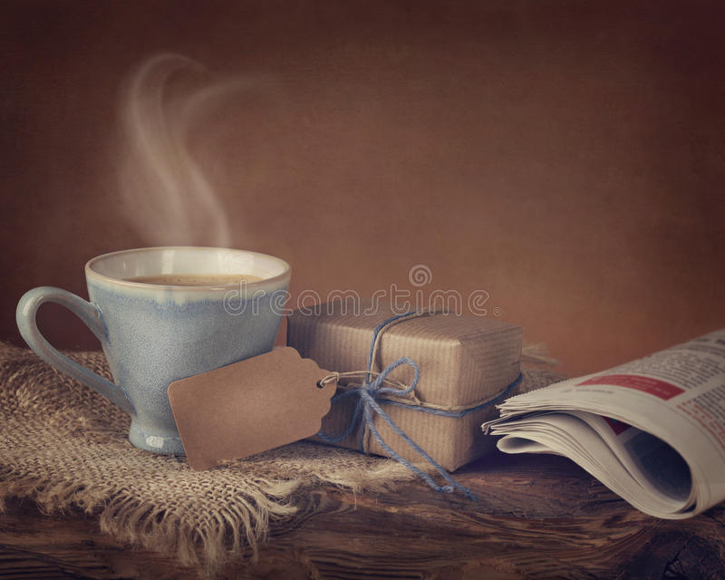 Gift box and a cup of coffee. Gift box with a tag and a cup of coffee stock photo