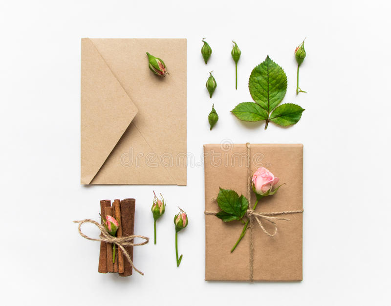 Gift box and envelope in eco paper on white background. Presents decorated with roses. Holiday concept, top view, flat lay. Vintage gift box and envelope in eco stock image
