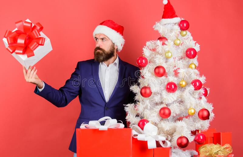 Gift box with festive ribbon bow falling right to male hand. Man bearded hipster formal suit happy celebrate christmas royalty free stock image