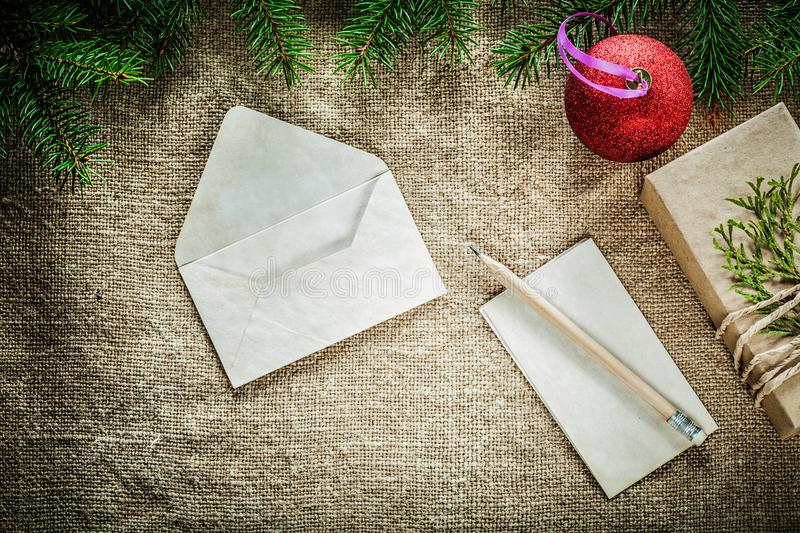 Gift box fir tree branch paper envelope pencil bauble on sacking stock images