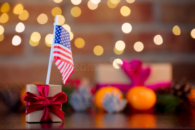 Gift box and flag of the USA. On background with fairy lights in bokeh. Christmas Holiday season royalty free stock photos