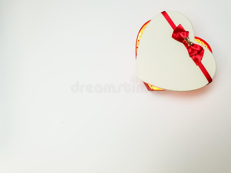 Gift box in the form of a heart with a red ribbon with a bow ajar with lights inside on a white background royalty free stock images