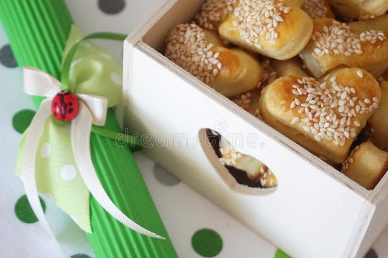Gift box full of healthy cookies sprinkled with sesame and decoration with bow and little ladybug stock image