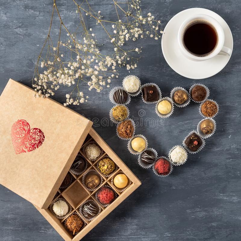 Gift box of gourmet chocolates for Valentine`s Day on dark background with cup of coffee, top view, copy space royalty free stock image