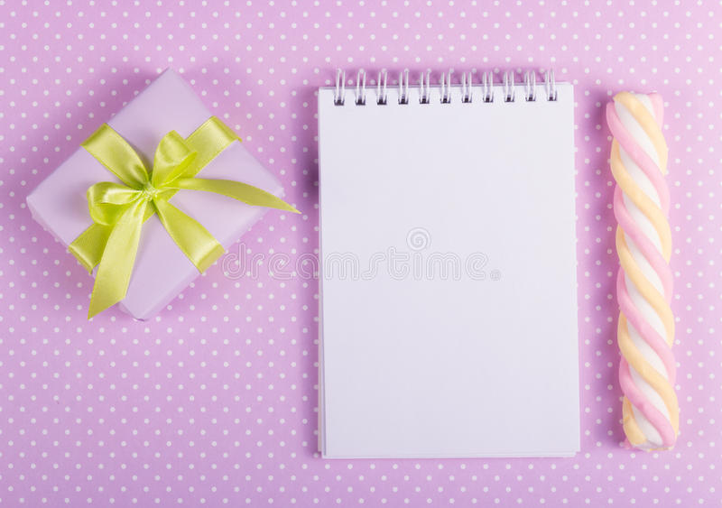 Gift box with green bow, open notebook with a blank page and stick marshmallows on a background of polka dots royalty free stock photo