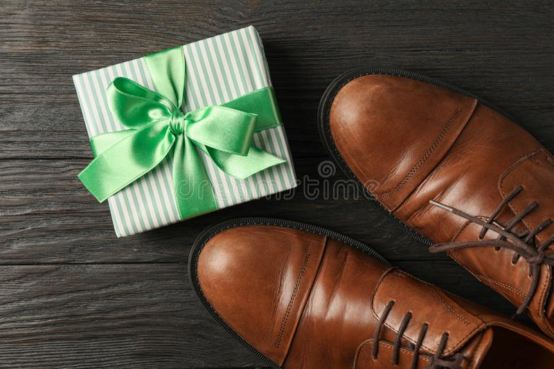 Gift box with green ribbon and brown leather shoes on wooden background, space for text royalty free stock images