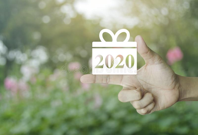 Gift box happy new year 2020 flat icon. On finger over blur pink flower and tree in park, Business shopping online concept stock image