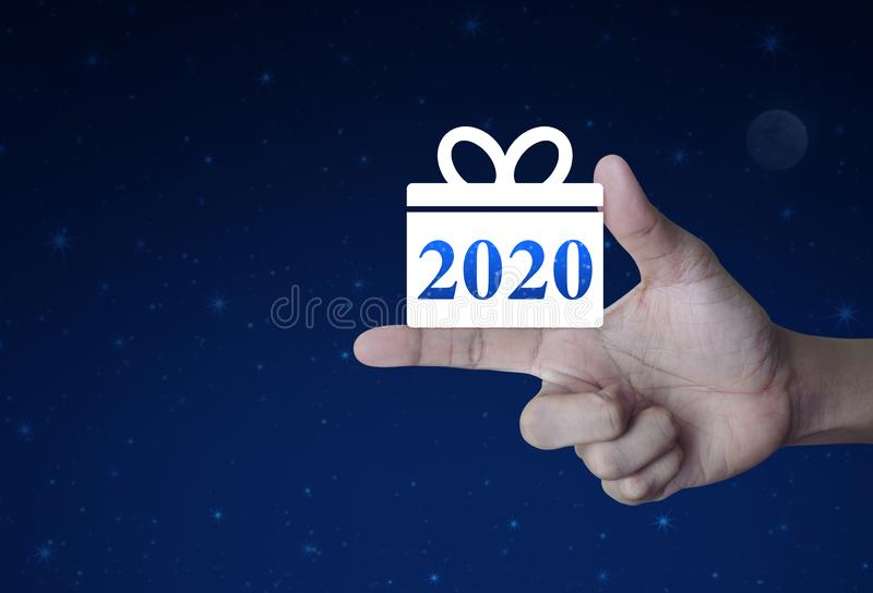 Gift box happy new year 2020 flat icon. On finger over fantasy night sky and moon, Business shopping online concept stock image