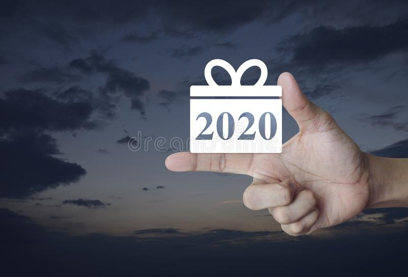 Gift box happy new year 2020 flat icon. On finger over sunset sky, Business shopping online concept royalty free stock photos