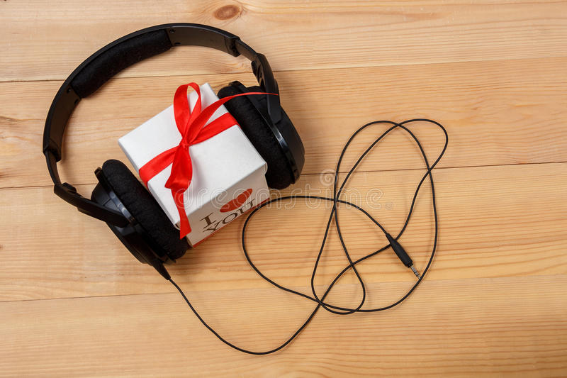 Gift box with headphones on wooden table. Top view stock image
