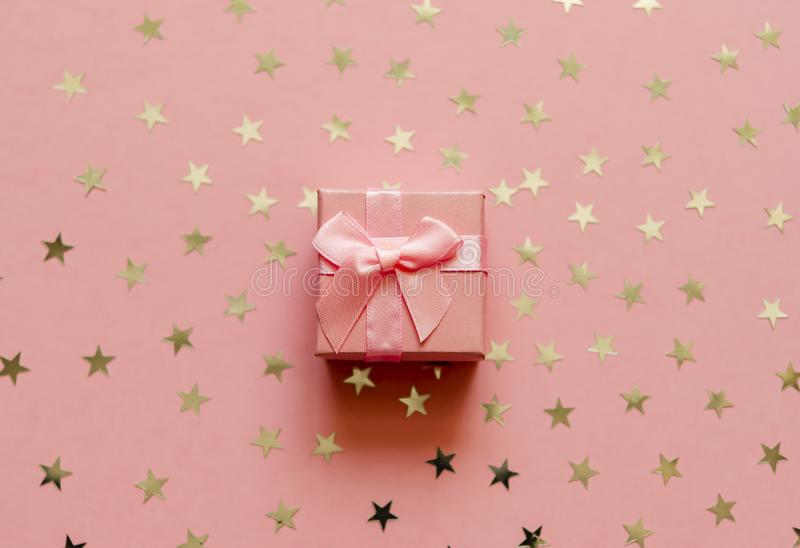 Gift box with holographic golden stars. Living Coral - Color of the Year 2019. Festive backdrop. Top view stock photo