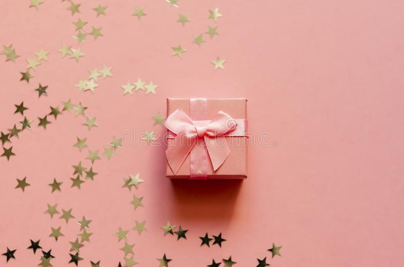 Gift box with holographic golden stars. Living Coral - Color of the Year 2019. Festive backdrop. Top view. Copy space. stock images