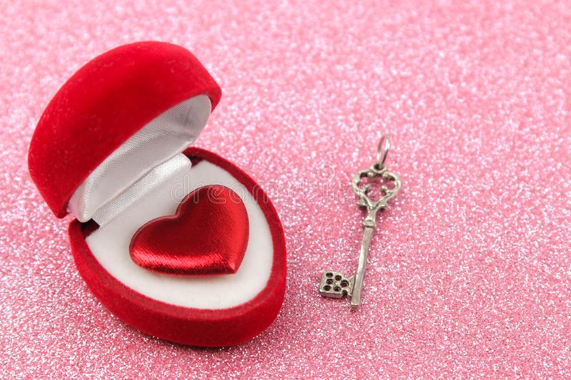 Gift box with key and red hearts close-up on a bright shiny pink background. Valentine`s Day stock photos