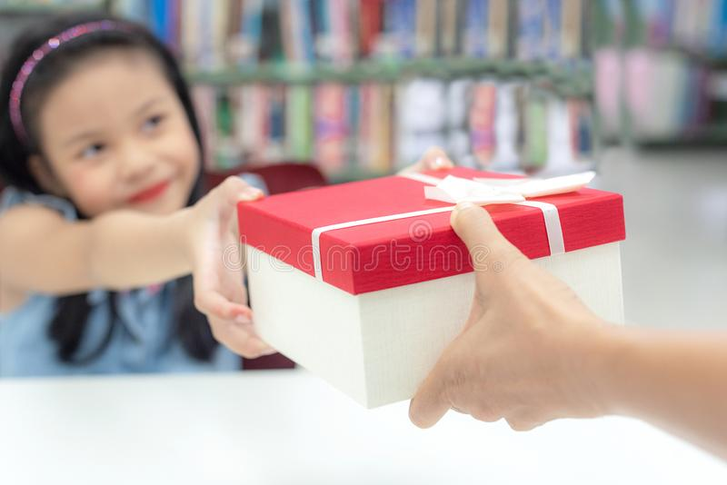 Gift box for kids girl. White box with red bow in the smiling asian girl hands for give a gift in the library. royalty free stock images