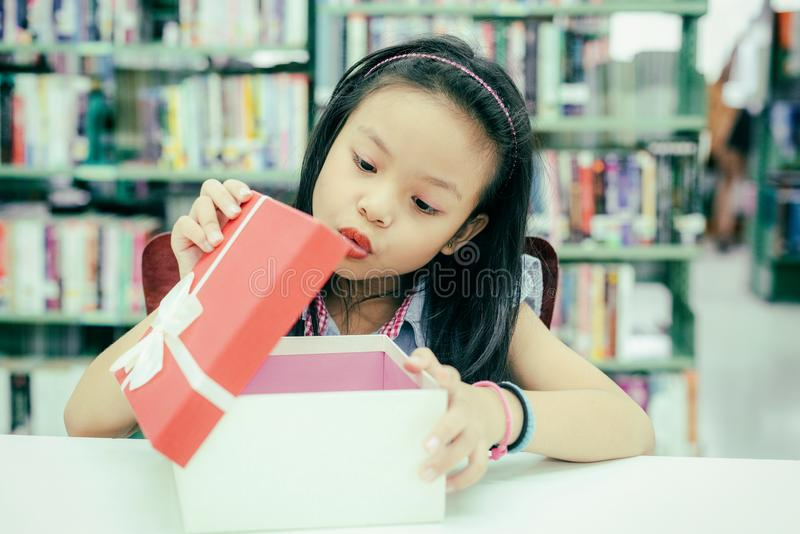 Gift box for kids girl. White box with red bow in the smiling asian girl hands for give a gift in the library, happy and surprise. Gift in the box.  Anniversary royalty free stock photography