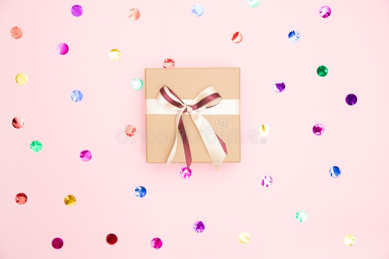 Gift box with kraft cardboard bow on pink background with confetti, top view. Surprise concept, birthday present stock photography