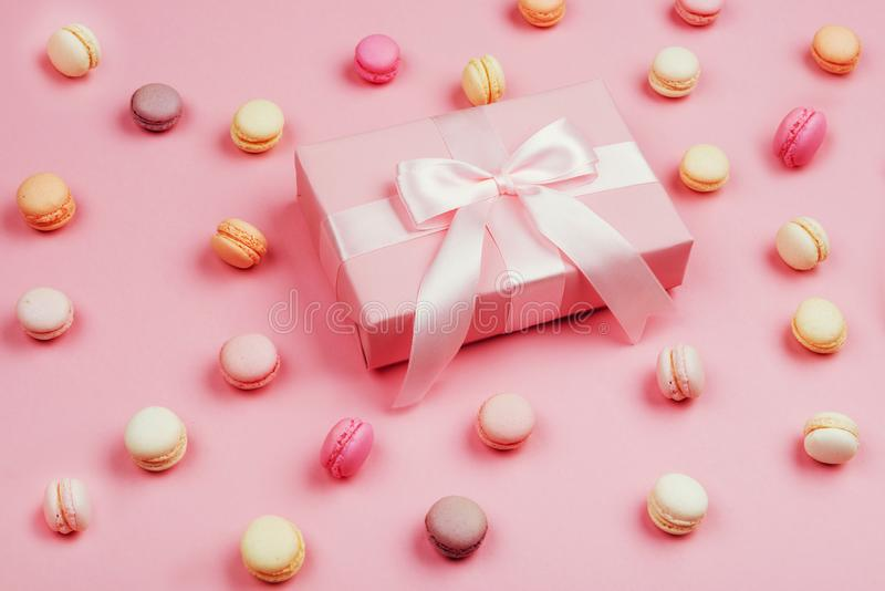 Gift box and macarons on pink background. With copy space to write stock images