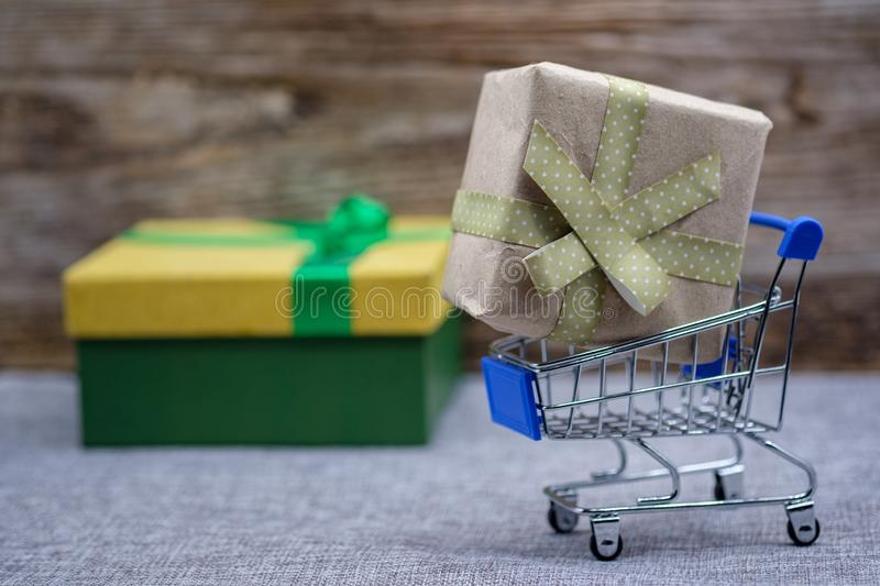 Gift box in the supermarket cart. the concept of buying a gift for the holiday royalty free stock photography