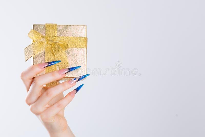 Gift box. Modern style blue stiletto Nail Polish. Beauty hands holding golden gift box. Stylish Colorful french navy Nails. Isolated white background.  Nail stock image