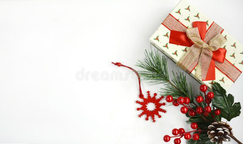 Gift box with multi-colored bow, decorative branch with red berries and a snowflake on a white background stock images