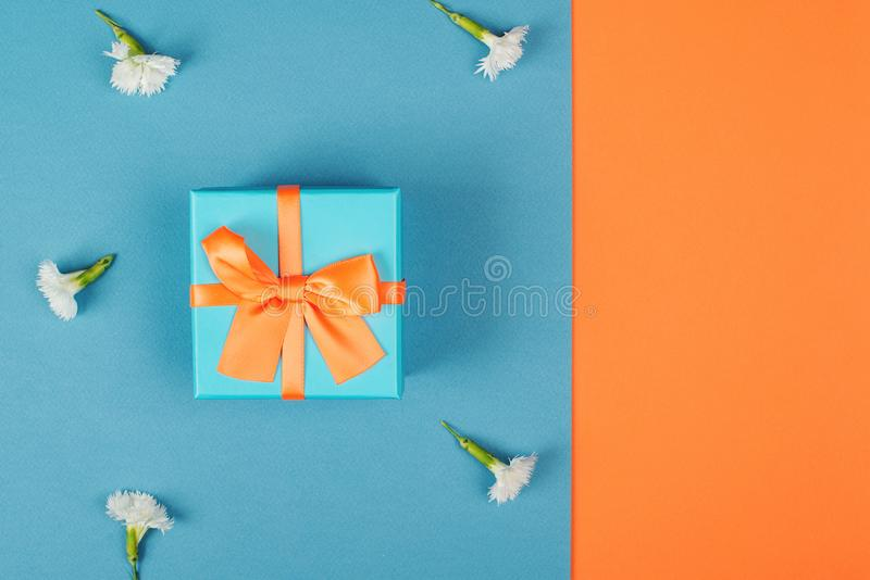 Gift box with orange bow on blue background with flowers, copy space. Flat lay. Top view. Minimal concept with wrapped present. Ho royalty free stock images