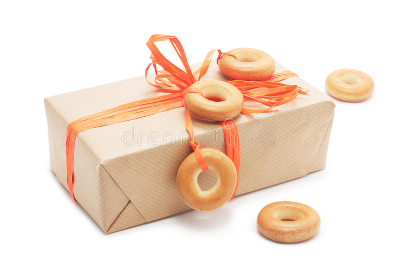 Gift box with orange ribbon and bagel royalty free stock photography