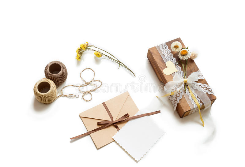 Gift box (package) with flowers, envelope with blank gift tag on white background royalty free stock photo