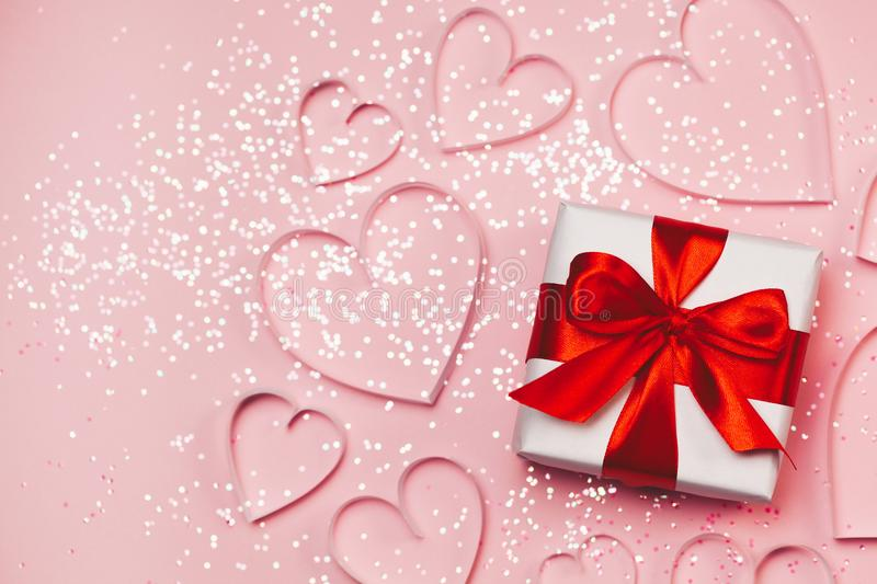 Gift box and paper hearts with sparkling glitter on pink background. Romantic st. Valentine`s day concept of greetings. Top view,. Flat lay royalty free stock photography