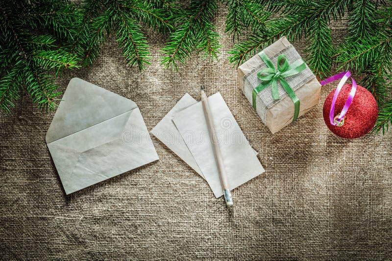 Gift box pine tree branch paper envelope pencil bauble on sackin royalty free stock photos