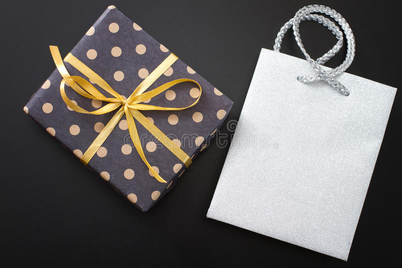 Gift box in polka dots and paper bag on black background. Top view and copy space royalty free stock photo