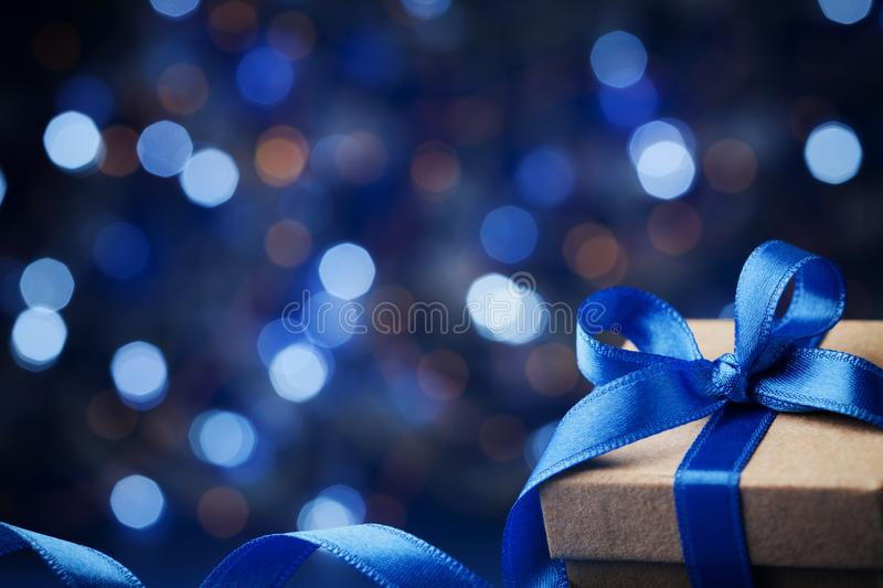 Gift box or present and christmas balls against blue bokeh background. Magic holiday greeting card. royalty free stock photo