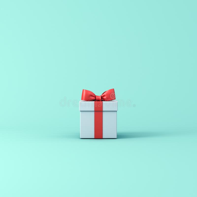 Gift box or Present box with red ribbon and bow isolated on light blue green pastel color background stock image
