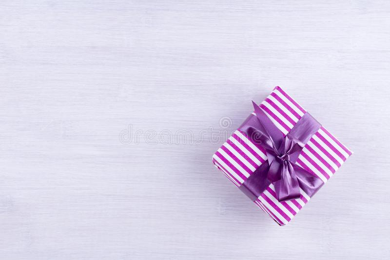 Gift box with purple ribbon on a light background. royalty free stock images