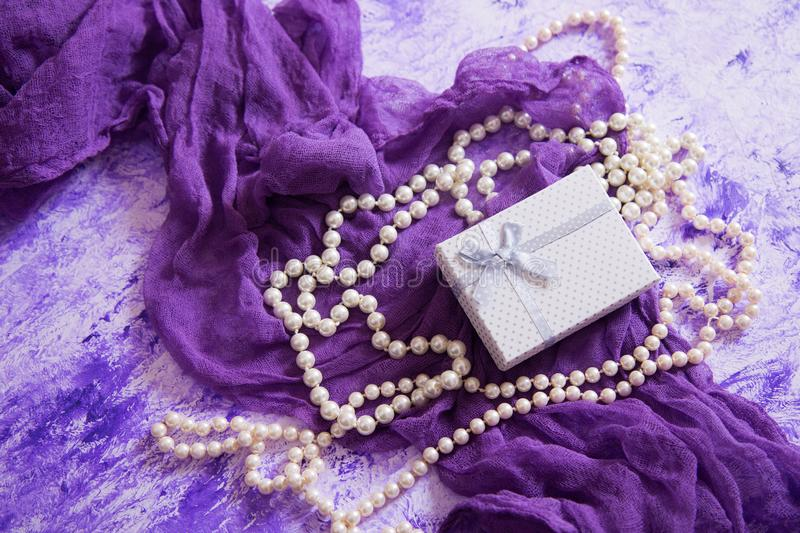 Gift box on purple tender fabric surrounded with white pearl necklace on marble table. High angle stock photos