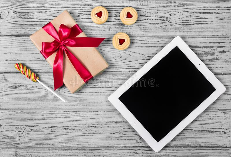 Gift box with red bow, heart cookies and tablet. Romantic concept. St. Valentine`s Day. Gift for Valentine`s Day. royalty free stock photography