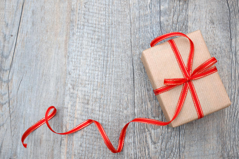 Gift box with red bow. On wood background stock images