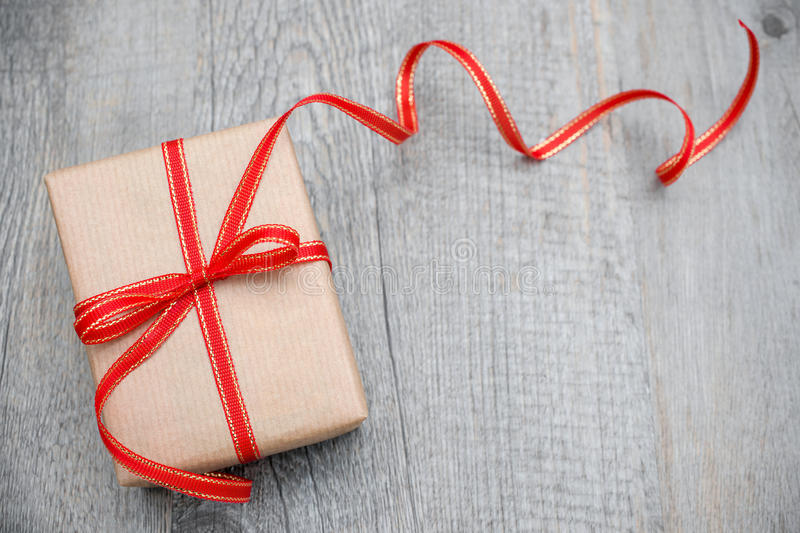 Gift box with red bow. On wood background royalty free stock images