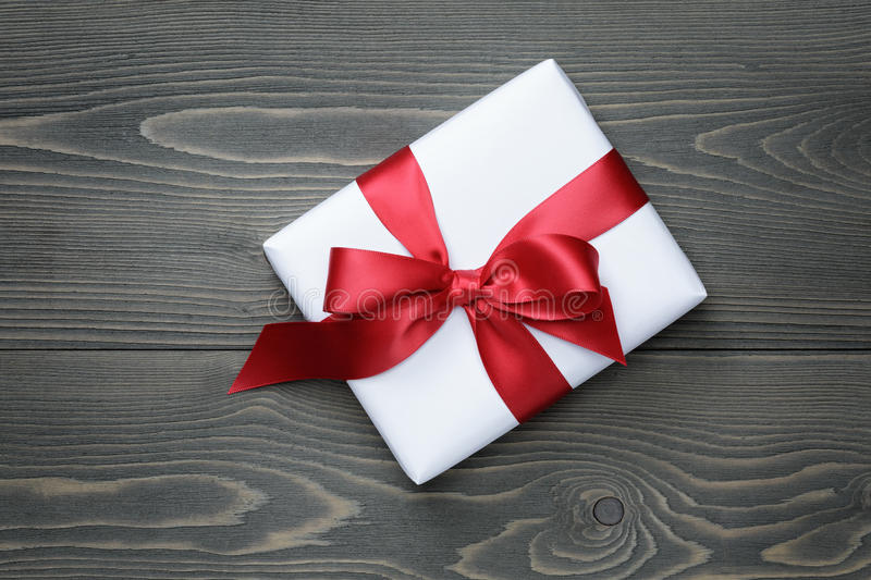 Gift box with red bow on wood table royalty free stock image