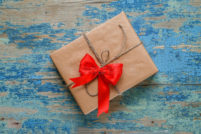 Gift box with a red bow. On wooden background with crackling effect stock image