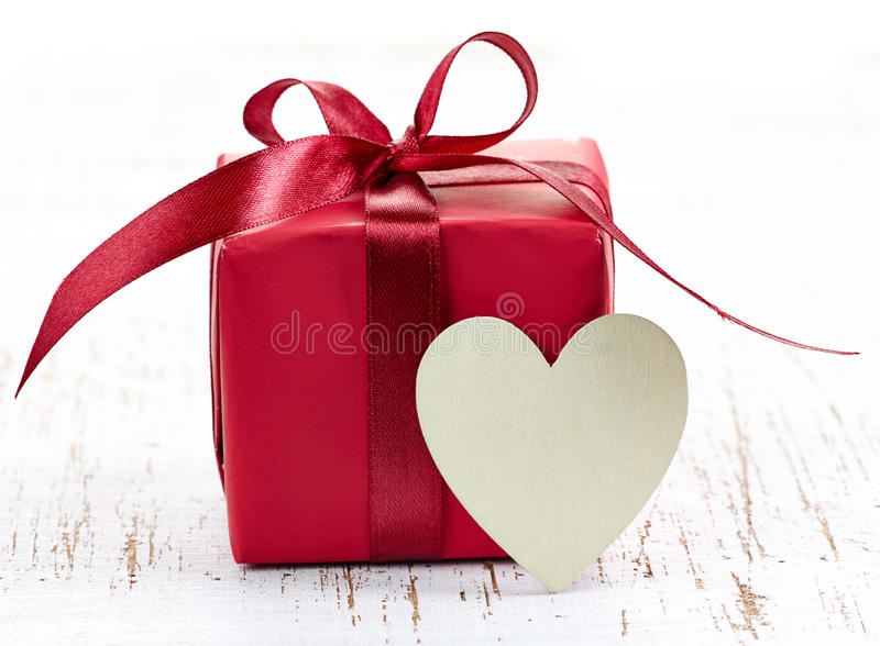 Gift box. Red gift box and heart (with space for text) on white wooden background stock image