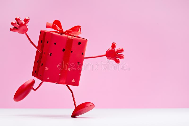 Unexpected congratulations. I am your gift! Running cheerful gift in red box. Gift in box. Red box on legs, with hands. Cartoon figure. Copy space stock image