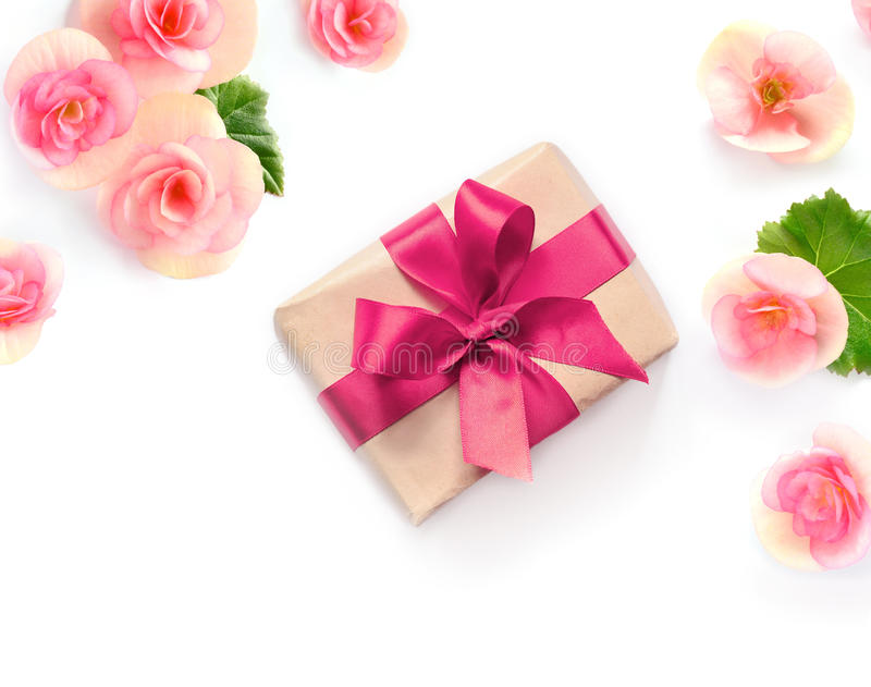 Gift box with red ribbon and bow on white with flowers background. flat lat, top view royalty free stock photos