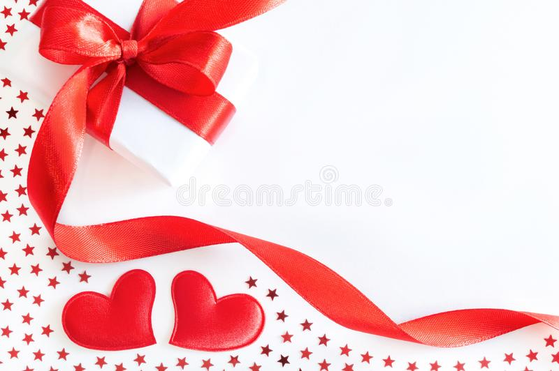 Gift box with red ribbon, decorative hearts and stars confetti on white background stock photos