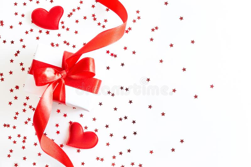 Gift box with red ribbon, decorative hearts and stars confetti on white background stock images