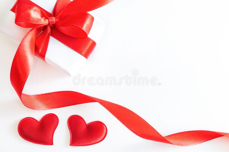 Gift box with red ribbon, and decorative hearts on white background stock image